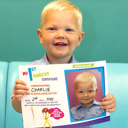 A young boy smiling and holding up his First Haircut Certificate from Snip-its.