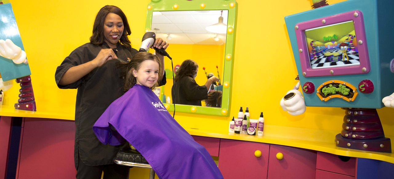 A young girl enjoying her haircut experience with a stylist at Snip-its.