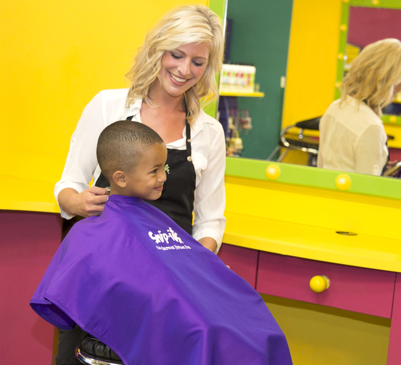 A young boy enjoying his haircut from a stylist at Snip-its.