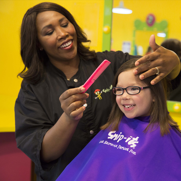 A young girl enjoying her haircut from a stylist at Snip-its.