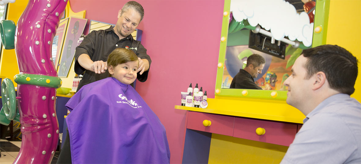 A young boy getting his hair cut by a Snip-its stylist with his dad sitting by and watching.