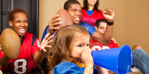 A family decked out in jerseys cheering while watching a football game.